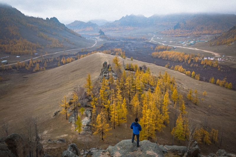 High Angle View Of Hiker Standing On Rock Against Landscape During Autumn