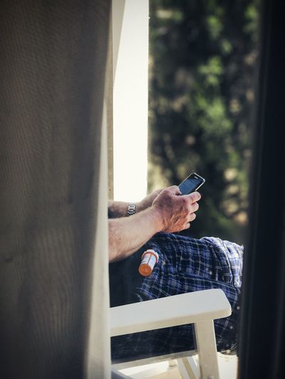 Midsection Of Man Using Phone While Sitting On Chair