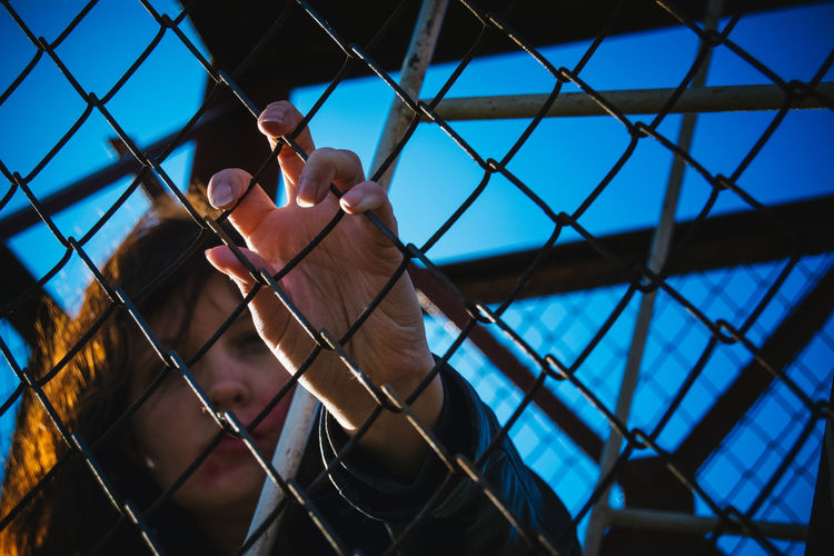 Woman holding chainlink fence against clear blue sky