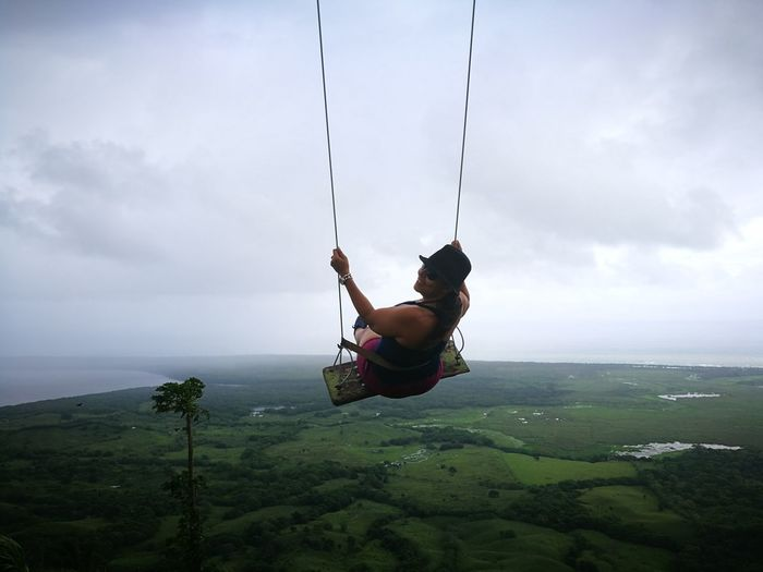Woman wearing hat looking over shoulder while swinging on swing against cloudy sky