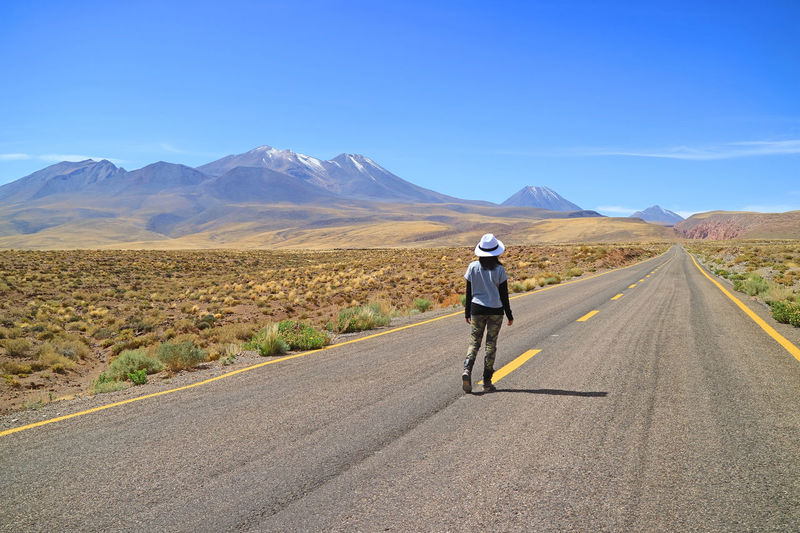 Rear view of woman walking on empty road against sky