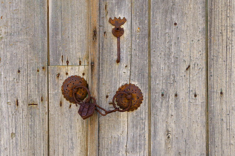 Close up of rusty old iron mountings with chain and padlock on a wooden double door Security Chain Close-up Decayed Beauty Door Door Chain Door Lock Doorlock Double Door Grunge Iron - Metal Iron Mountings Lock Locked Door Metal Mountings Old Padlock Rusted Rusty Rusty Metal Secure Vintage Wood - Material Wooden