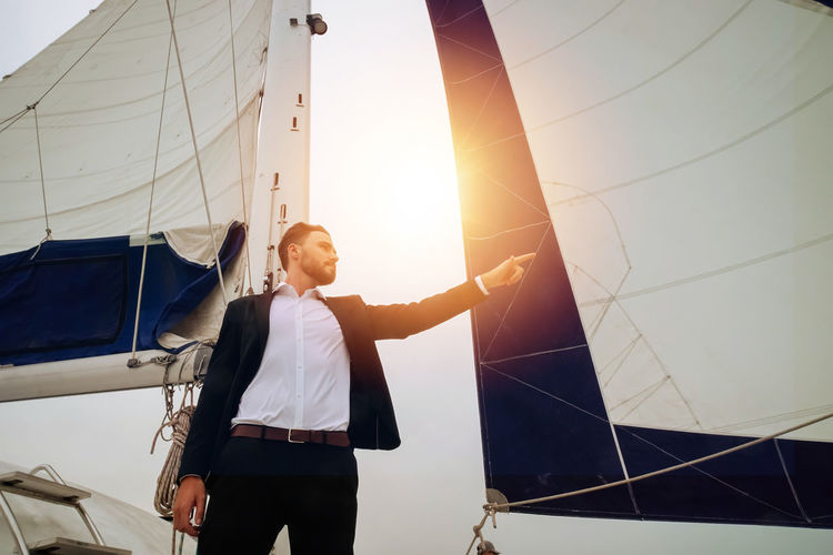Man standing on sailboat against sky