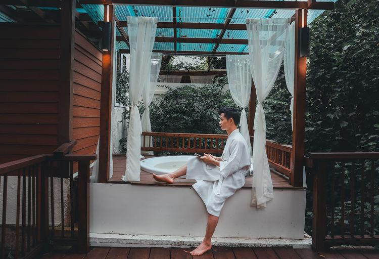 Young man wearing bathrobe sitting by hot tub