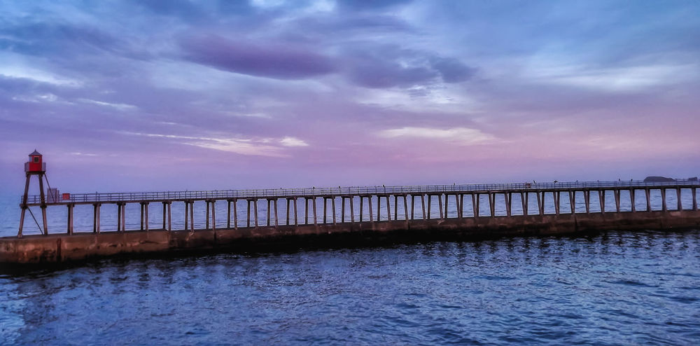 Sunset over one of Whitby Piers Sky Dusk Sea Travel Destinations Cloud - Sky Sunset Horizon Over Water Water Whitby Pier Whitby Whitbypiers Whitby North Yorkshire Creative Light And Shadow Color Photography Fujifilm Creative Light And Shadow Built Structure Sunset_collection