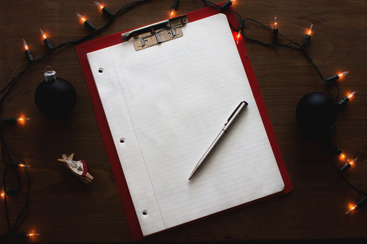 High angle view of illuminated string light by lined paper on clipboard at table