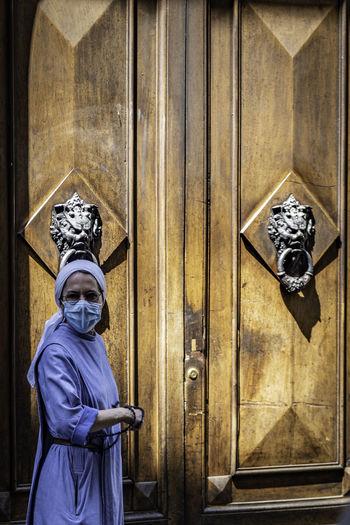 Portrait of person wearing mask against door