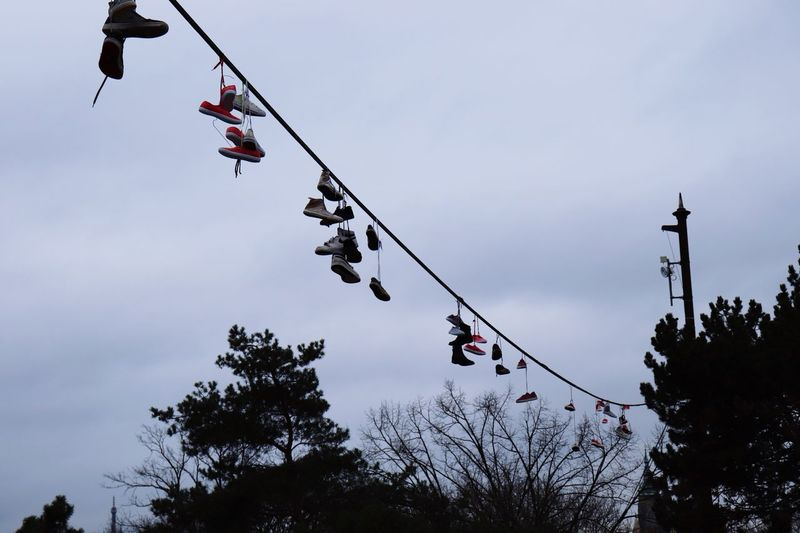 Low angle view of shoes hanging from cable against sky