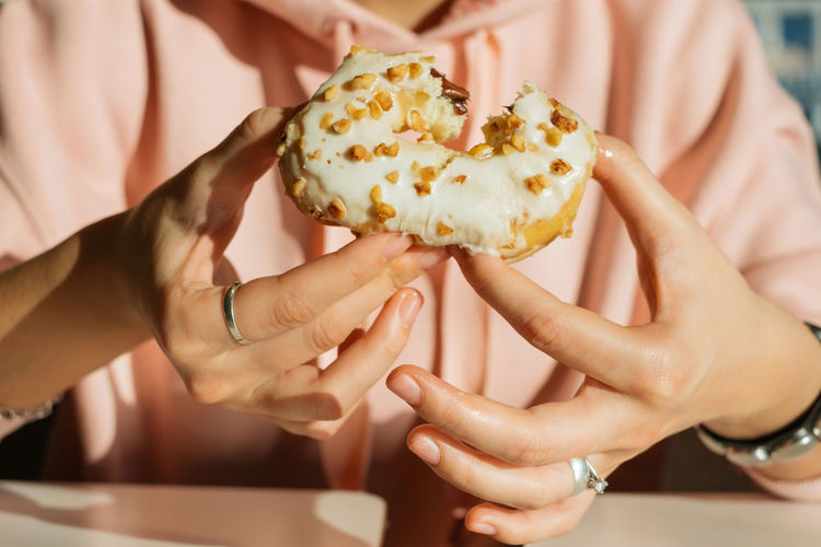 Midsection of woman eating donut at table