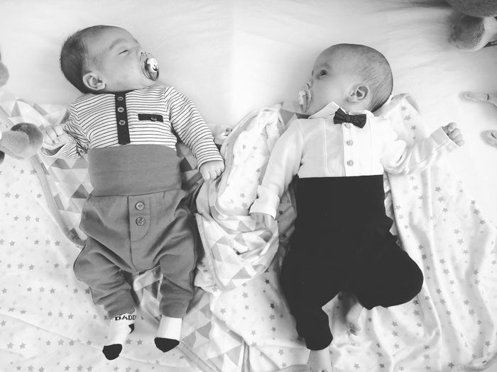 Directly Above Shot Of Newborn Brothers Lying On Bed