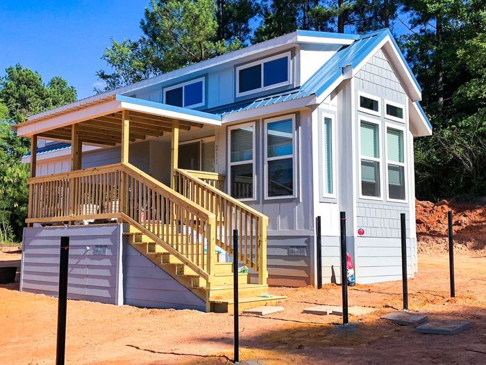 Tiny house Roof Country Living Stairs Steps Porch Blue Color Tiny House On Wheels Minimalist Small House Architecture Built Structure Tree Sunlight Building Exterior Plant Nature Day Shadow No People Outdoors Sky Wood - Material Sunny Building House Railing Security Safety Gate