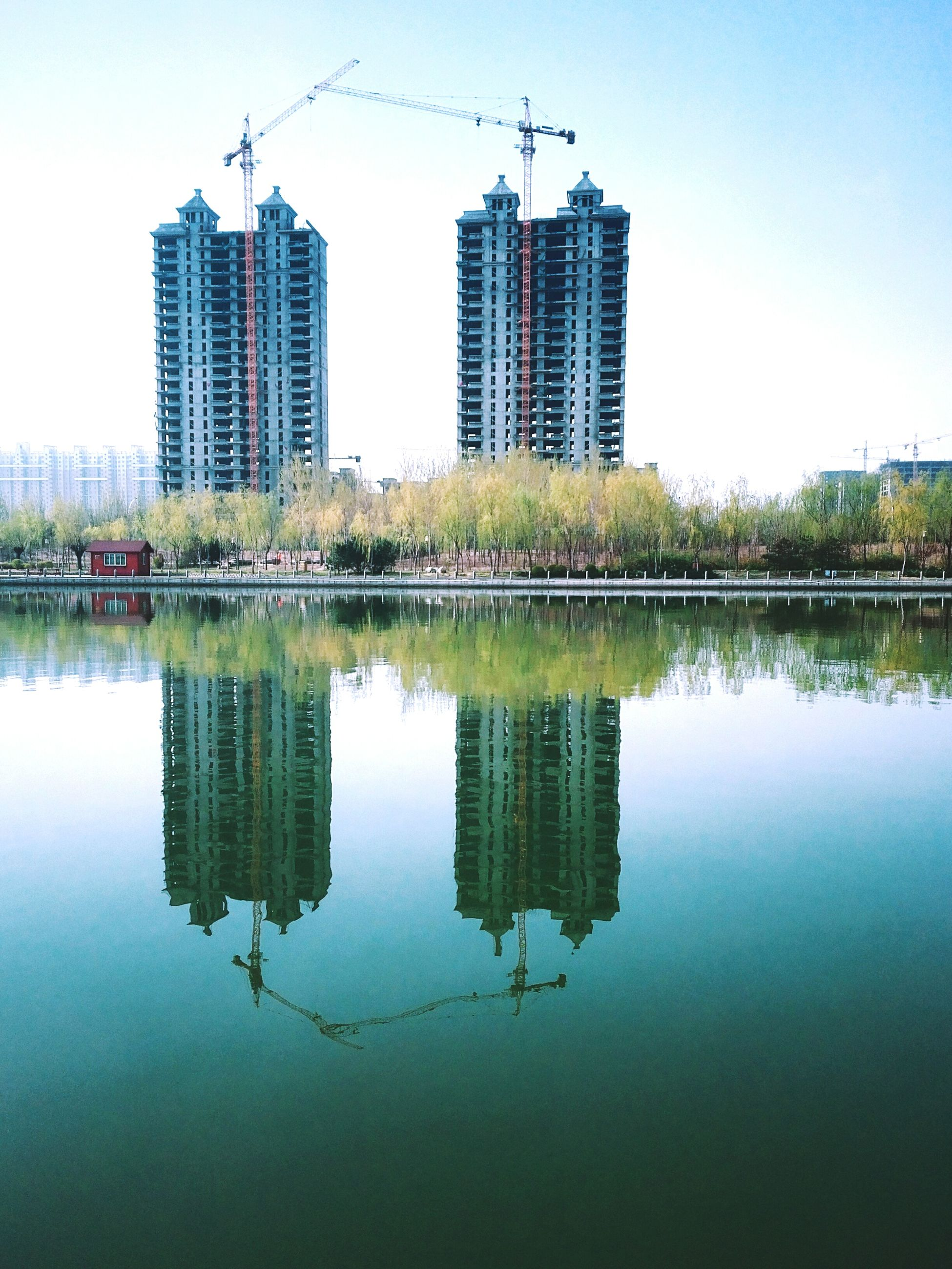 architecture, reflection, water, built structure, building exterior, waterfront, city, river, clear sky, connection, skyscraper, lake, tower, modern, building, standing water, sky, office building, day, outdoors