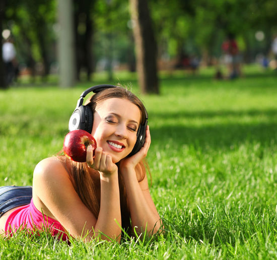 Woman with headphones listening music on the grass Outdoors Hairstyle Beautiful Woman Nature Lifestyles Adult Cheerful Lying On Front Emotion Headphones Portrait Green Color Relaxation Young Adult Leisure Activity Women Lying Down One Person Happiness Plant Grass Smiling Field Real People Young Women Day