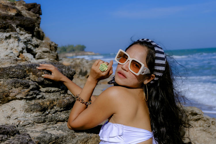 Young woman wearing sunglasses on rock at beach against sky