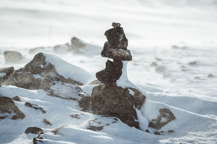 Stacked Rocks On Snow Covered Field During Winter