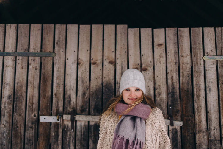 Portrait of smiling woman standing against fence during winter