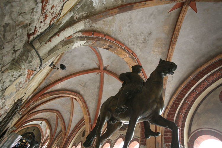 Low angle view of equestrian statue against ribbed vault ceiling in church corridor
