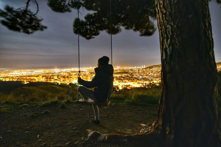 Side view of silhouette mature man looking at illuminated cityscape while swinging on mountain at night