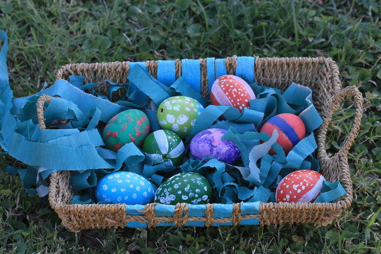 High angle view of multi colored eggs on field
