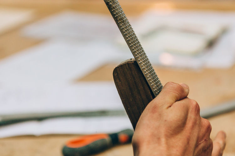 Close up on the hands of a carpenter using a manual lime