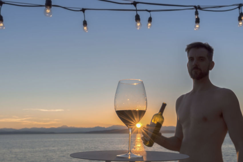 Red wine at sunset with shirtless caucasian male holding wine bottle in background by the sea. Cruise Ship Mediterranean  Service Shirtless Sunburst Al Fresco Alcohol Balcony Beach Bottle Caucasian Crystal Deck Hanging Lights Luxury Ocean Resort Sailing Sea Stemware Sunset Tipping Waiter Wealth Wine