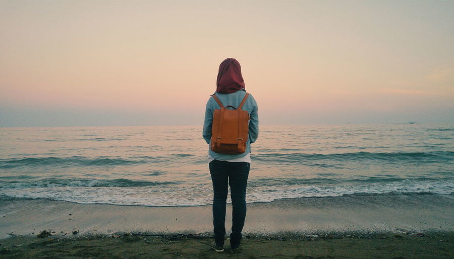 Rear View Of Woman Standing At Sea Shore Against Sky During Sunset