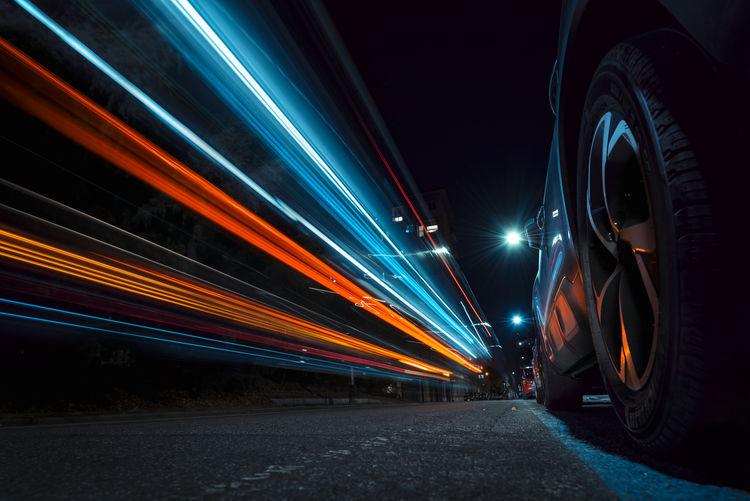 Light trails of hybrid vehicle from the ground. car, asphalt.