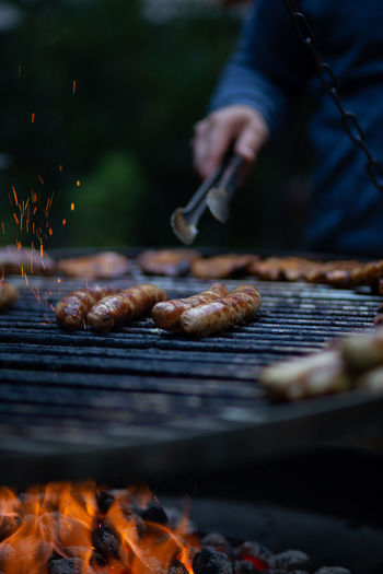 Person holding tongs with sausage on barbecue grill