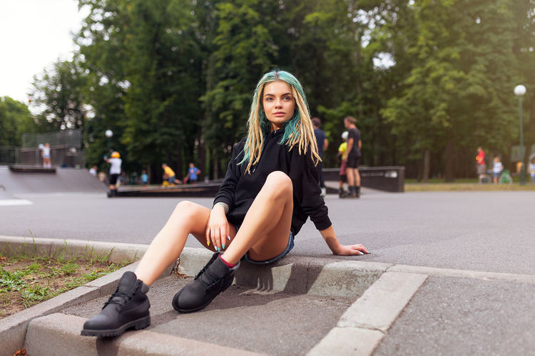 Young Woman Sitting On Footpath