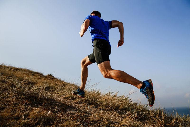 Full length of man running on hill against sky