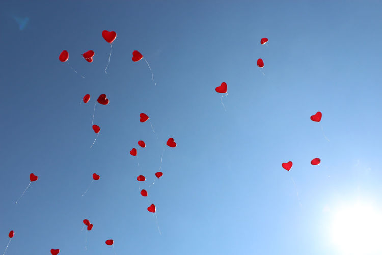 Low angle view of heart shape balloons flying against blue sky