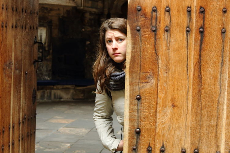 Portrait Of Scared Woman Standing By Wooden Door