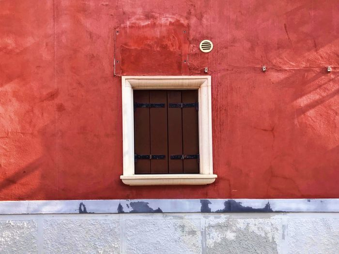 Window amidst red wall