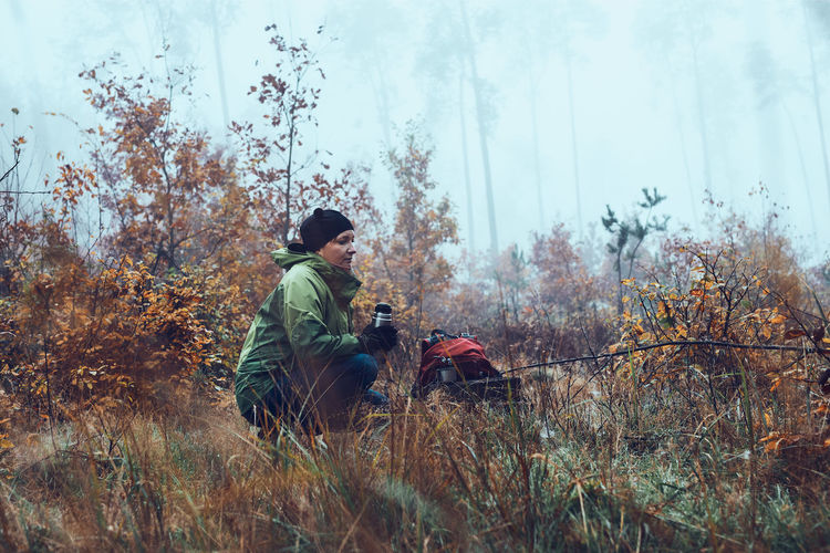 Woman with backpack having break during autumn trip drinking a hot drink from thermos flask