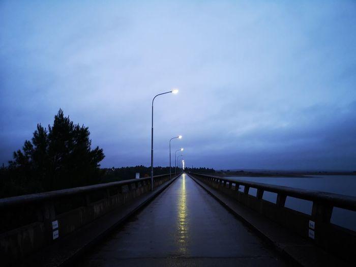 Street lights on bridge against sky at dusk