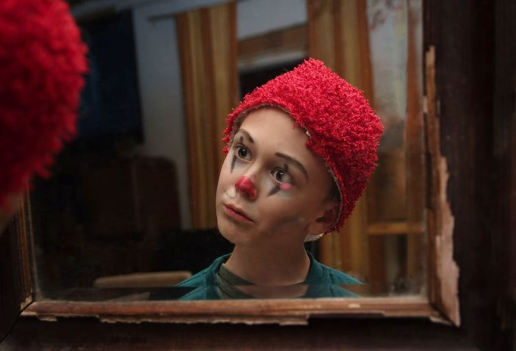 Portrait of boy clown painted face looking at mirror