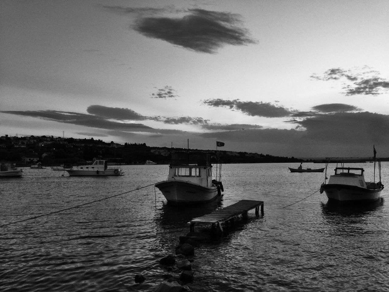 Boats Moored On Shore Against Cloudy Sky