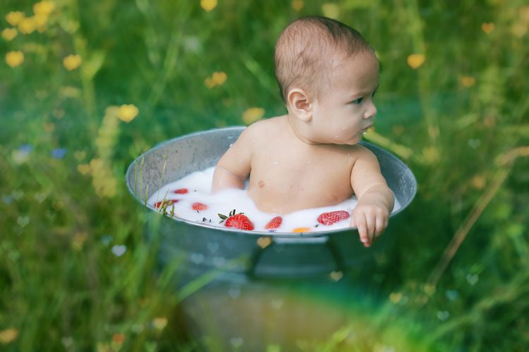 Cute shirtless baby girl sitting in bucket