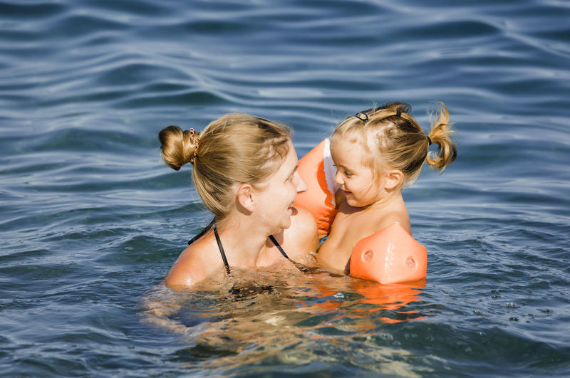 Smiling mother with daughter swimming in sea