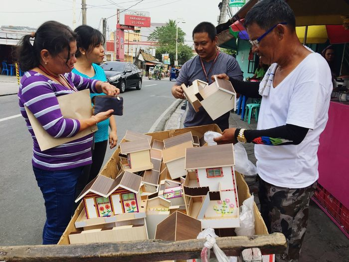 "Fifty-year-old entrepreneur Fernando Cabiles (R) sells ""houses"" on his pushcart in Taguig, Metro Manila. The houses are actually coin bank or 'alkansya' which his family assembles in Cavite, south of Manila. A single-detached house costs 60 pesos ($1.20), a duplex costs 130 pesos (about $2.60) while a two-storey house sells for 230 pesos ($4.60). City People Occupation Outdoors Adult Day Adults Only Entrepreneur Handicraft Coinbank Piggy Bank Philippines Taguig Manila"