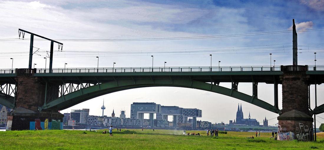 Arch bridge in city against sky