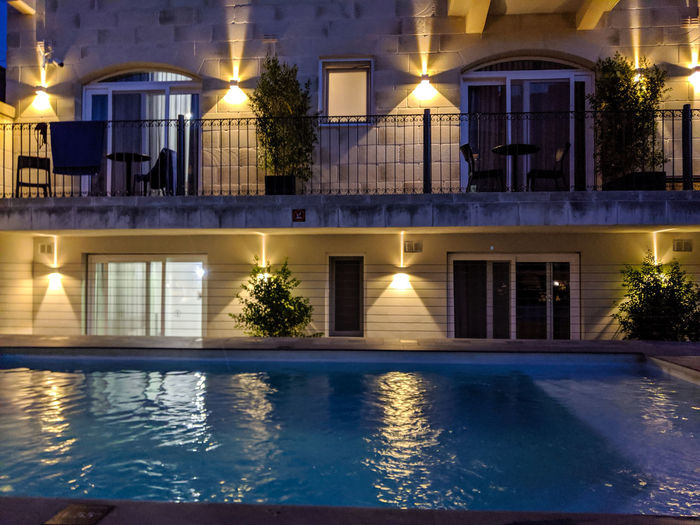 Reflection of illuminated building in swimming pool at night