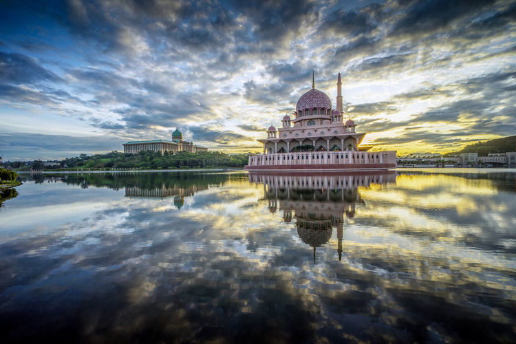 Mosque by lake during sunset