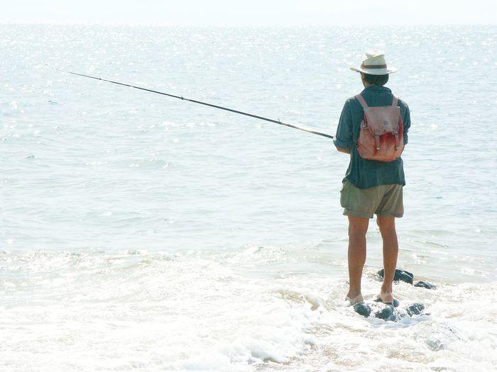 Rear view of man fishing on beach