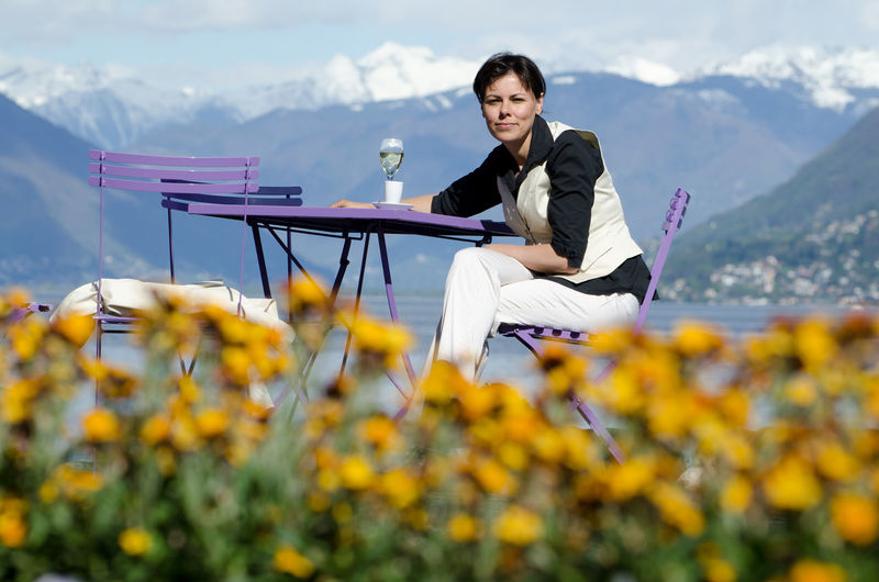 Woman Sitting in a Table with Snow-Capped Mountain and Drinking Champagne in Switzerland. Champagne Looking At Camera Snow-capped Woman Beauty In Nature Cloud - Sky Day Flower Freshness Lifestyles Mountain Mountain Range Nature One Person One Woman Only Outdoors People Real People Scenics Selective Focus Sitting Sky Smiling Swiss Alps Well-dressed