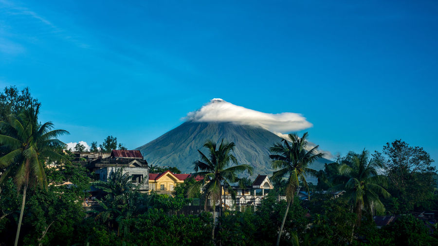 Distant view of Mayon Volcano, Legazpi, Philippines with small cloud cover with houses and palm trees in the fore ground. Active Volcano Beauty In Nature Blue Cloud Cover Clouds Green Landscape Houses Landscape Landscape_Collection Mount Mayon Mountain Nature Outdoors Palm Tree Philippines Plant Scenics Sky Symmetrical Travel Destinations Tree Volcanic Landscape Volcano