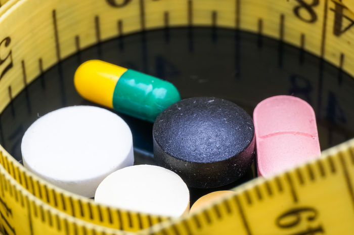 colorful of a medication and measurement tape isolated on black Diet Isolated Reflection Background Black Close-up Colorful Concept Day Healthy Indoors  Measurement Tape Medication Medications Multi Colored No People Pill