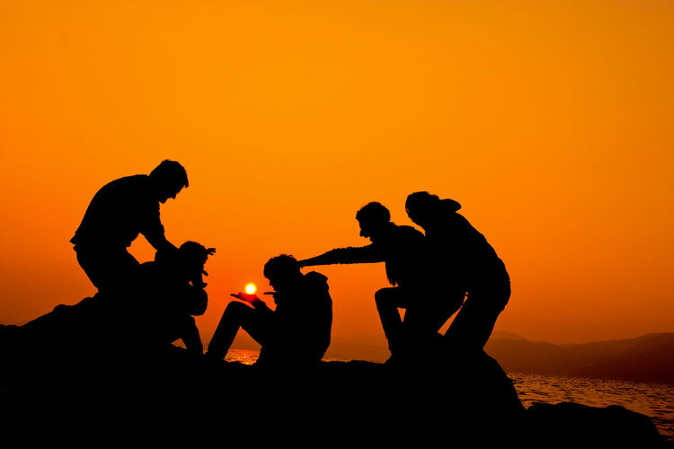 Beauty In Nature Friendship Group Of People Land Leisure Activity Lifestyles Men Nature Orange Color Outdoors People Real People Rock Scenics - Nature Sea Silhouette Sky Sunset Togetherness Water