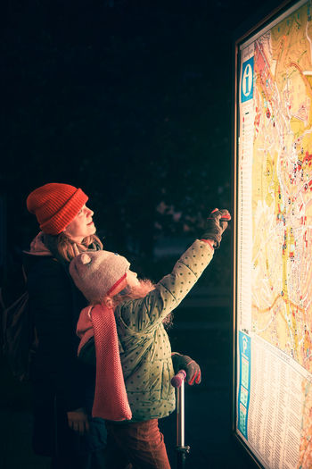 Mother and child waring in warm clothing looking for the way on a city map.
