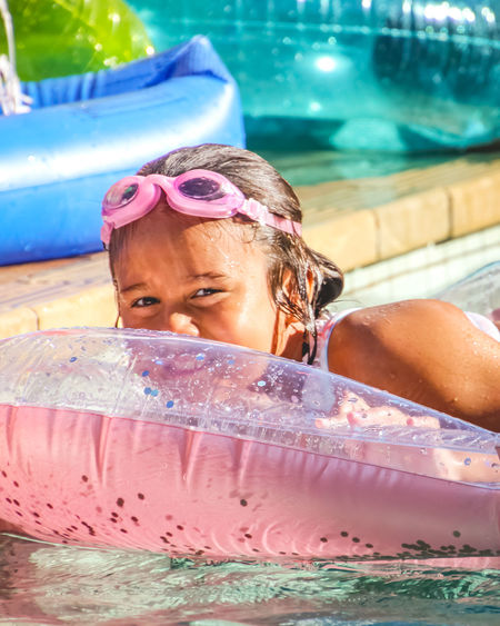 portrait of a young girl relaxing in the pool on pink inflatable Water Pool Swimming Pool Headshot One Person Portrait Real People Leisure Activity Females Child Swimming Childhood Lifestyles Front View Swimwear Girls Innocence Inflatable  Outdoors Eyewear Innocence Swimming Goggles Pink Color Diversity